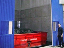 Dust enclosure for shakeout with powered doors and roof access for crane
